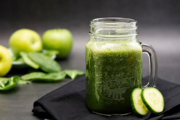 Smoothie verde saudável em uma foto escura do alimento da caneca do frasco de pedreiro. conceito de comida saudável.