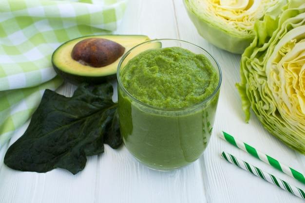Smoothie verde vegetariano com abacate, spihach e repolho no fundo branco de madeira