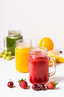 Smoothie vermelho, amarelo e verde em uma jarra de vidro e ingredientes.