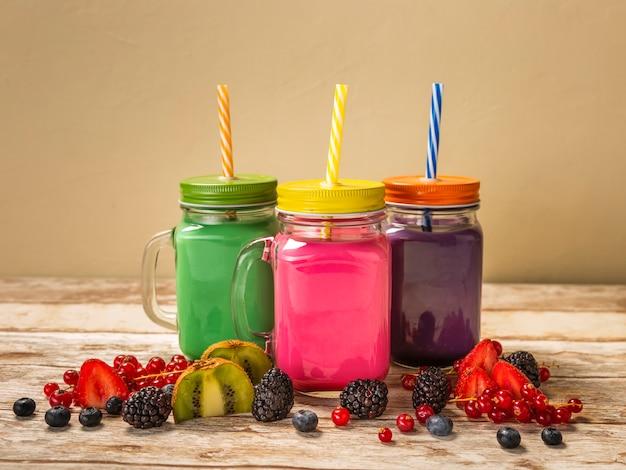 Smoothies coloridos de vista frontal em frascos