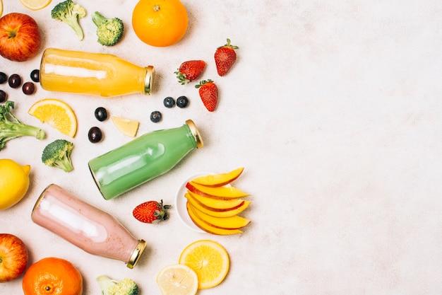 Smoothies coloridos planos e frutas com cópia espaço