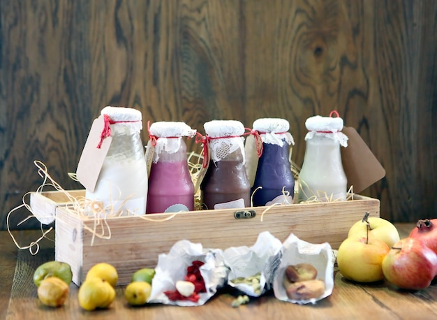 Smoothies coloridos saudáveis em garrafas com frutas bebem milk-shake em caixa de madeira com ingredientes