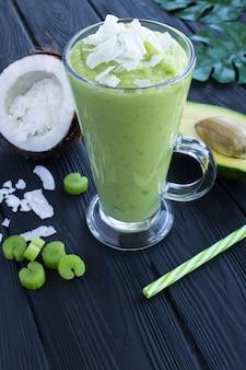 Smoothies com abacate, leite de coco e aipo na mesa tropical.