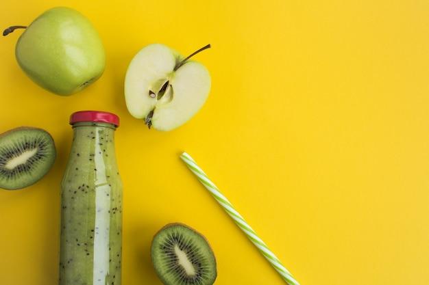 Smoothies com kiwi e maçãs verdes no frasco de vidro no fundo amarelo. vista superior. copie o espaço.