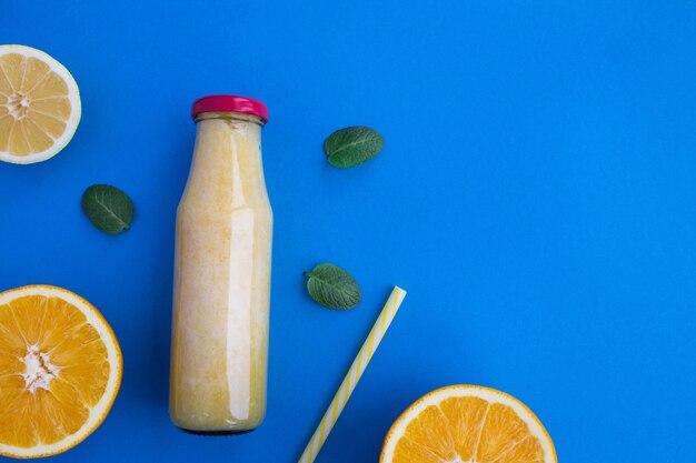 Smoothies com laranja e limão no frasco de vidro sobre o fundo azul. vista superior. copie o espaço.
