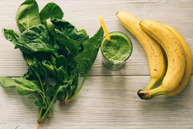 Smoothies com uma palha, uma banana e folhas de espinafre no fundo de madeira branco