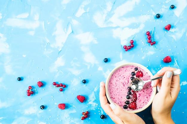 Smoothies de berry com passas e framboesas sobre um fundo azul brilhante