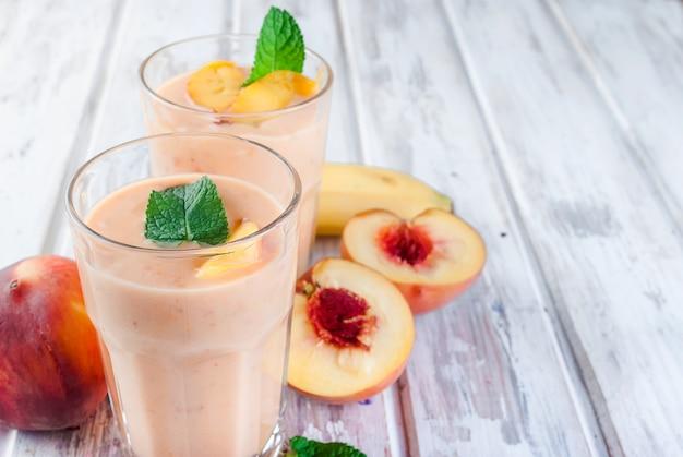 Smoothies de berry de damasco, pêssego e banana em copos e ingredientes em uma mesa de madeira