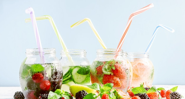 Smoothies de desintoxicação de frutas e legumes frescos em potes de vidro com tubos