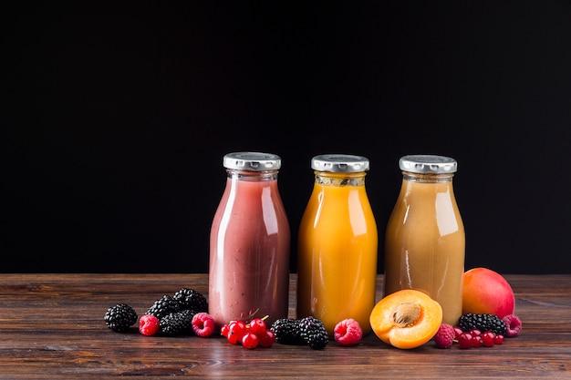 Smoothies de frutas e pêssego na superfície de madeira