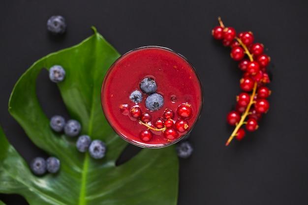 Smoothies de frutas na folha contra fundo preto