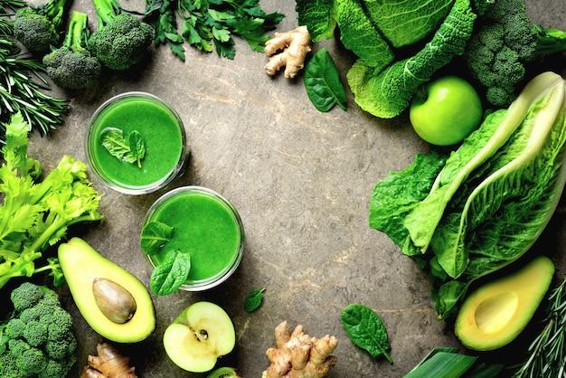 Smoothies de frutas verdes e vegetais folhosos em dois copos, bebida de vitamina verde para desintoxicação e dieta magra, espaço em branco para um texto, vista de cima