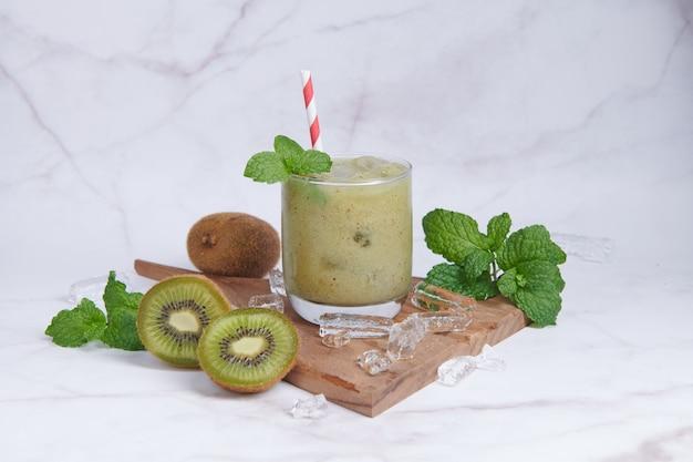 Smoothies de kiwi caseiros frescos com leite, hortelã e mel. bebida orgânica saudável. close-up e foco seletivo. fruta verde acabada de misturar, conceito de bem-estar e emagrecimento.