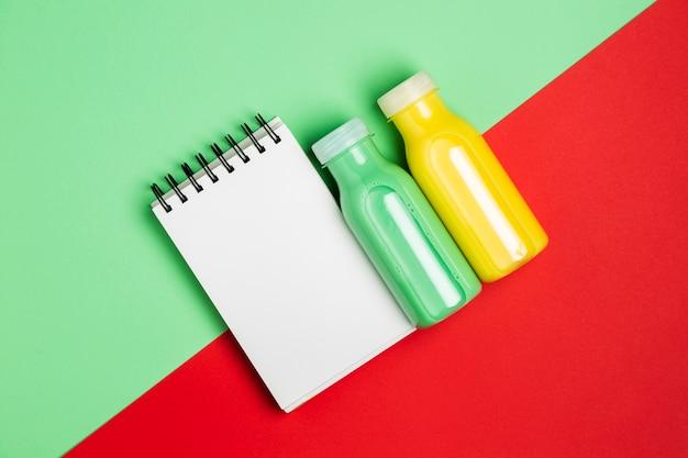 Smoothies de laranja e verdes com o bloco de notas vazio