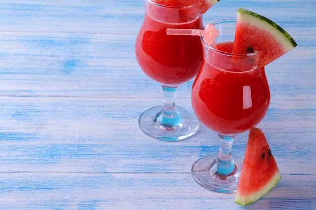Smoothies de melancia ao lado de fatias maduras de melancia em uma mesa de madeira azul