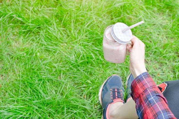 Smoothies de morango na mão feminina em um fundo de relva verde