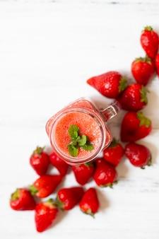 Smoothies de morango ou morangos com gelo em uma jarra. uma bebida refrescante de verão. fundo branco. vista do topo. copie o espaço
