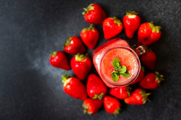 Smoothies de morango ou morangos com gelo em uma jarra. uma bebida refrescante de verão. fundo preto. vista do topo. copie o espaço