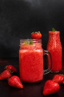 Smoothies de morango ou morangos com gelo em uma jarra. uma bebida refrescante de verão. fundo preto. vista frontal. copie o espaço