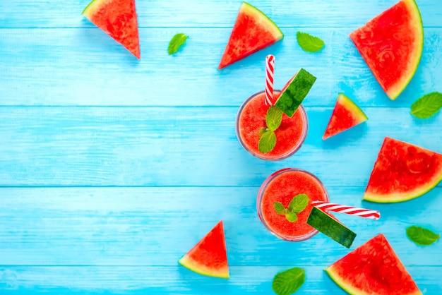 Smoothies de suco de melancia nos óculos sobre fundo de madeira azul claro