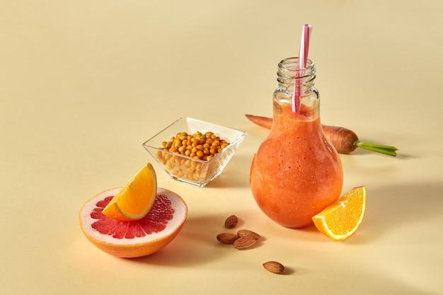 Smoothies de toranja de cenouras frescas com laranja, espinheiro e amêndoas em um copo sobre um fundo de papel amarelo. bebida desintoxicante