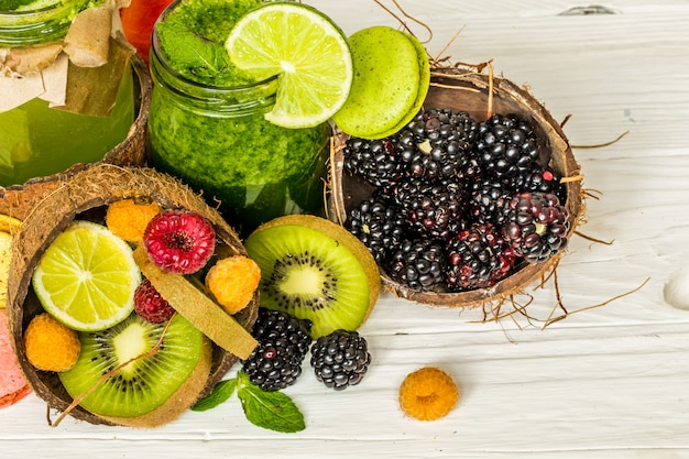 Smoothies de verdes e vermelhos em uma jarra com limão