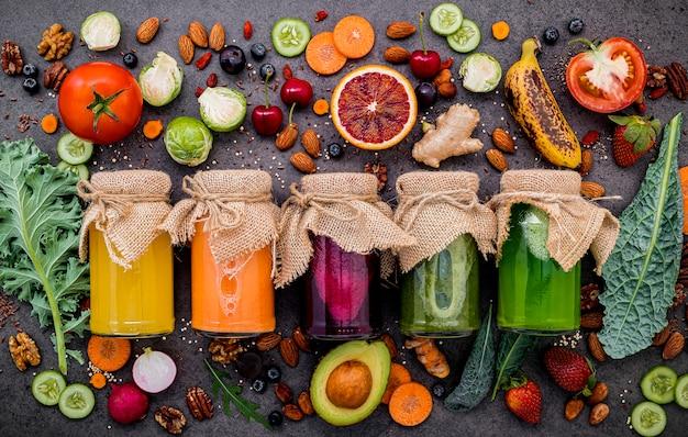 Smoothies e sucos saudáveis coloridos em garrafas com frutas tropicais e superalimentos no fundo de pedra escuro com espaço da cópia.