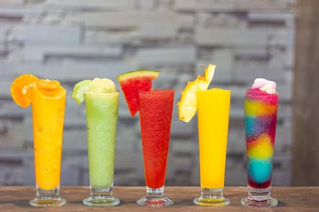 Smoothies frescos coloridos com frutas tropicais em fundo cinza