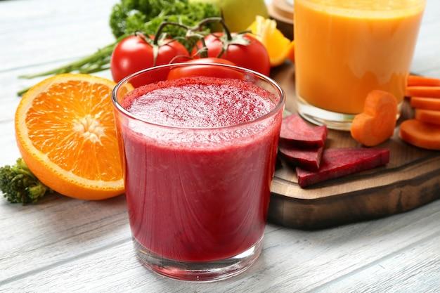 Smoothies frescos, legumes e uma fatia de laranja na mesa