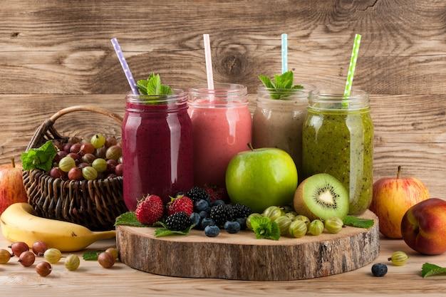 Smoothies, frutas e bagas em fundo de madeira