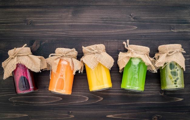 Smoothies saudáveis coloridos e sucos em garrafas com frutas tropicais e superalimentos na madeira