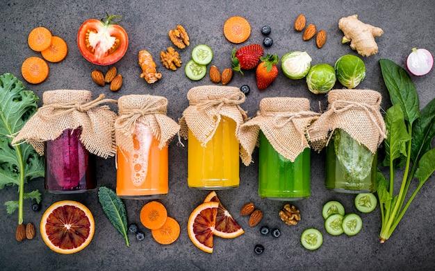 Smoothies saudáveis coloridos e sucos em garrafas com frutas tropicais e superalimentos na pedra escura