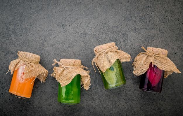 Smoothies saudáveis coloridos e sucos em garrafas no fundo escuro de pedra com espaço de cópia.