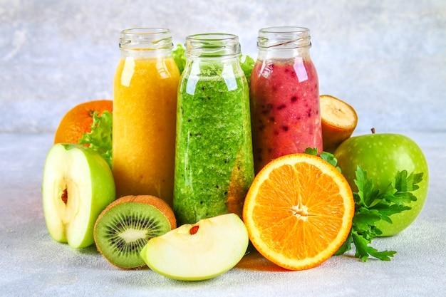 Smoothies verdes, amarelos, roxos em garrafas de groselha, salsa, maçã, kiwi, laranja, sobre uma mesa cinza.