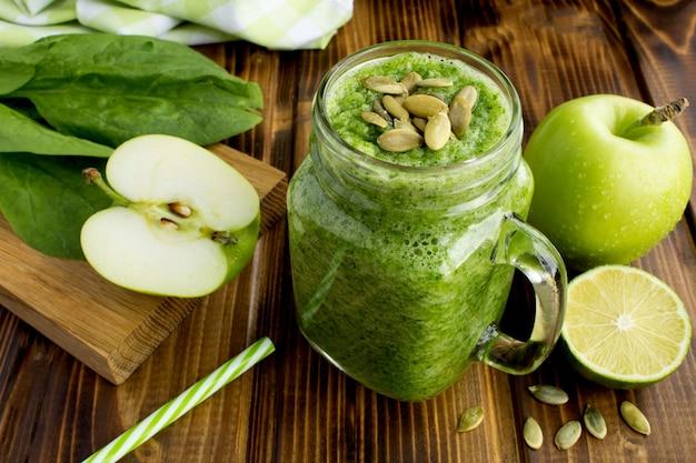 Smoothies verdes com sementes de espinafre, maçã e abóbora no fundo de madeira marrom