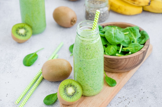Smoothies verdes dietéticos frescos de sementes de espinafre, banana, kiwi, iogurte e chia em potes de vidro com canudo