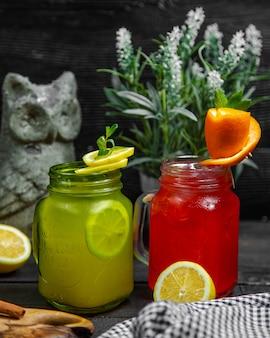 Smoothies verdes e vermelhos com rodelas de limão dentro de frascos.