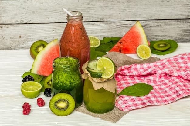 Smoothies verdes e vermelhos em uma jarra com limão, kiwi