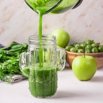 Smoothies verdes são derramados de um copo de liquidificador de vidro