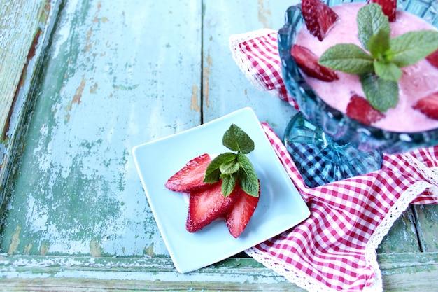 Smootie stawberry com decoração de hortelã em uma tigela de vidro turquesa sobre uma mesa de madeira com espaço de cópia