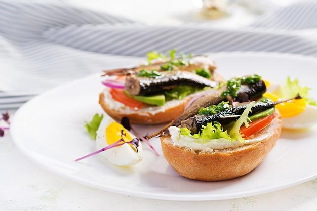 Smorrebrod com espadilha, abacate, tomate, ovos e cream cheese em prato branco