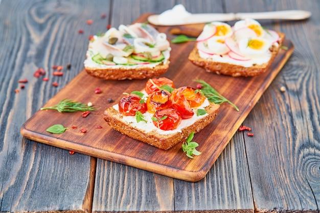 Smorrebrod - sanduíches dinamarqueses tradicionais. pão de centeio preto com peixe, arenque, ovo