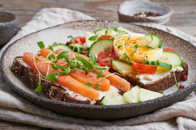 Smorrebrod - sanduíches dinamarqueses tradicionais. pão de centeio preto com salmão, cream cheese, pepino