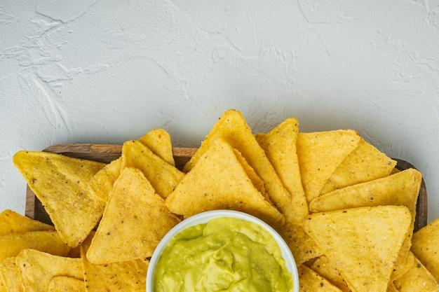 Snack crocante mexicano, nachos chips e molho de abacate guacamole de queijo, em mesa branca, vista de cima ou plano