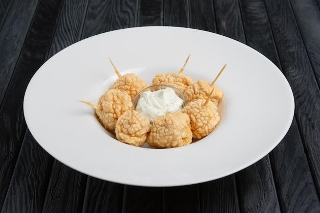 Snack para cerveja - bolas de queijo frito com molho.