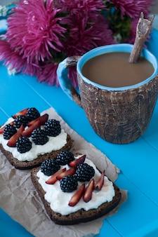 Sndwiches com queijo doce e frutas, uma xícara de café e um buquê de ásteres na superfície de madeira azul