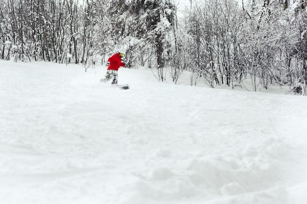 Snoboarder faz uma curva de casco indo para baixo na neve