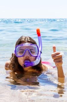 Snorkel menina com óculos e um tubo para nadar nas férias de verão