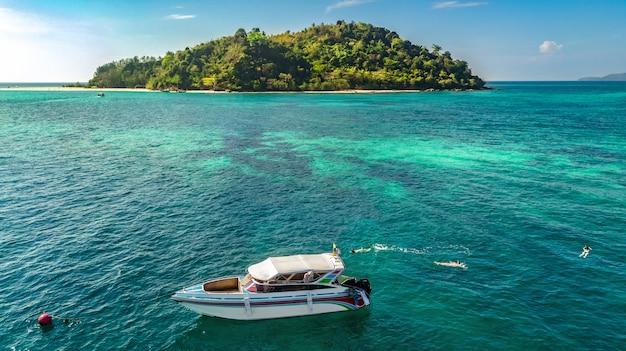 Snorkeling perto de barco no mar tropical claro, vista aérea de cima, mãe e filhos snorkelers nadando na água com corais nas férias de verão na tailândia