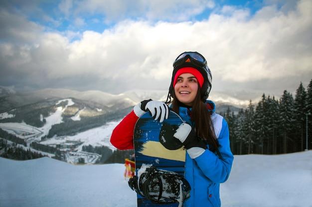 Snowboarder alegre mulher no inverno na estação de esqui
